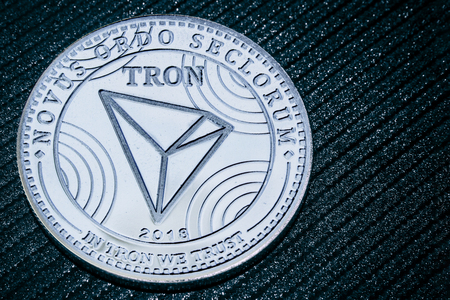 Coin cryptocurrency Tron on a grey shiny background. TRX. Фото со стока