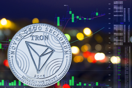 Coin cryptocurrency TRON on night city background and chart.