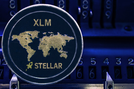 Coin cryptocurrency XLM and the numbers of the arithmometer. The concept of production or rate of Stellar. Stock Photo