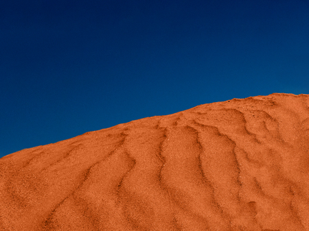 Ripples of red sand in the desert and blue sky. Imagens