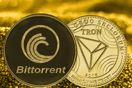 Coins cryptocurrency Bittorrent TRON and gold fabric background.