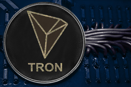 The coin cryptocurrency Tron on the background of wires and circuits. Token TRX. Фото со стока