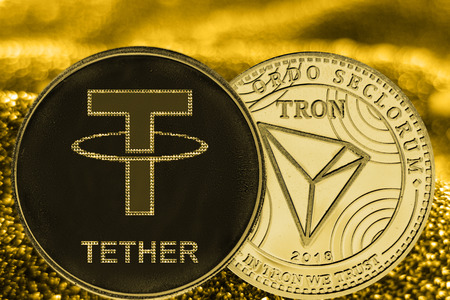 Coins cryptocurrency Tether TRON and gold fabric background.