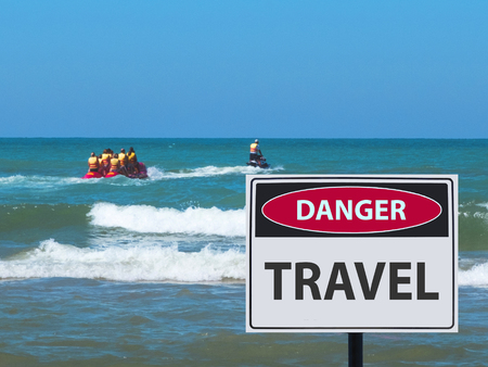 banana boat ride with tourists and the danger travel sign on the beach.