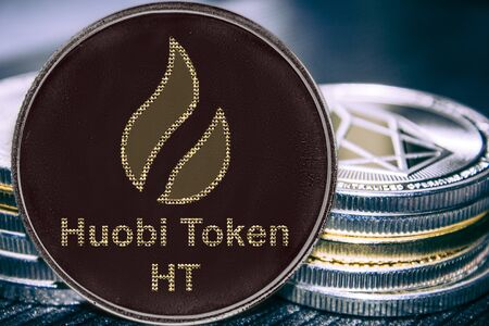 Coin cryptocurrency huobi token ht on the background of a stack of coins.