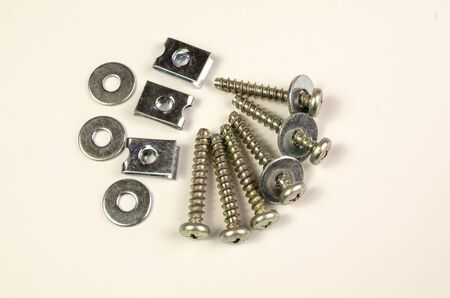 Close-up shot on a white background. Several automotive screws and washers holding a bunch.