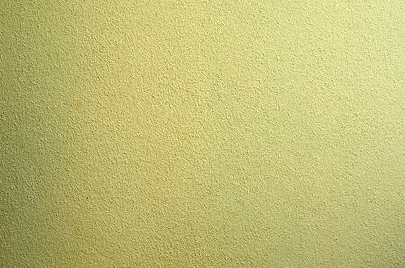 old wall plastered with cement and painted yellow
