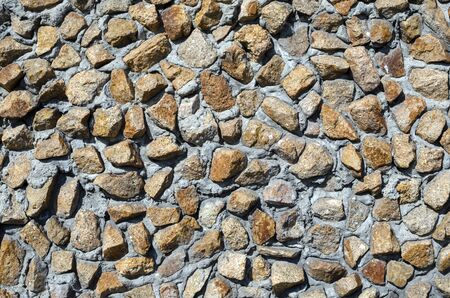 Background of stone. The stone wall is beige. Natural stone. The old wall. Background fragments of different sizes and textures