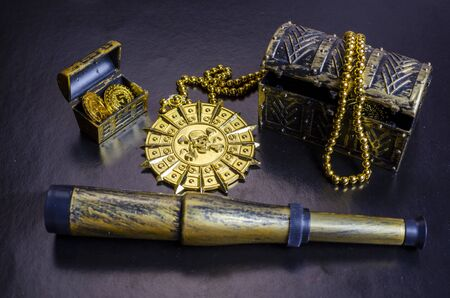 pirate treasure chest, gold pirate medallion and spyglass on a black background