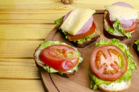 fresh sandwich with sausage and lettuce on a wooden stand Standard-Bild