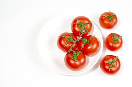 red tomatoes in a shallow plate on a white background. close-up