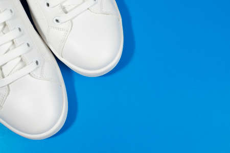 White sneakers isolated on blue background.