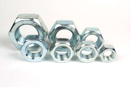 several metal nuts on a white background