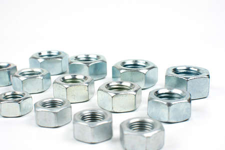 group of silver metal nuts close up on white background