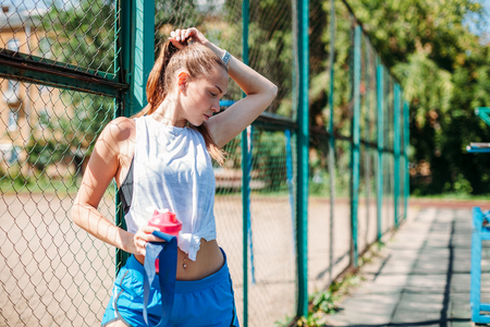 portrait of a sporty young sexy woman with a bottle of cool water on the summer sports field. Healthy lifestyle concept 스톡 콘텐츠