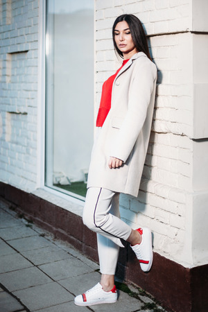 portrait of young beautiful brunette woman standing near white brick wall outdoors in urban background