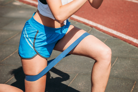 close-up of fitness elastic band on legs of young woman outdoors