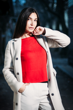 beautiful young brunette woman in red blouse white coat in evening outdoors