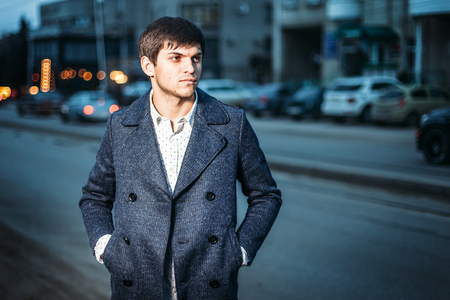 portrait of a young man in a coat and a white shirt on the street in the city. evening