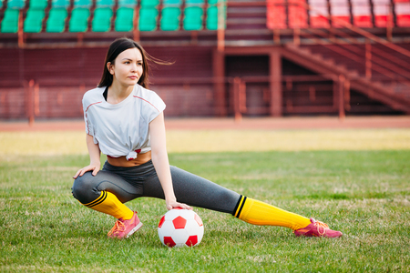 Athletic young sexy girl on the football field with the ball on a sunny summer day