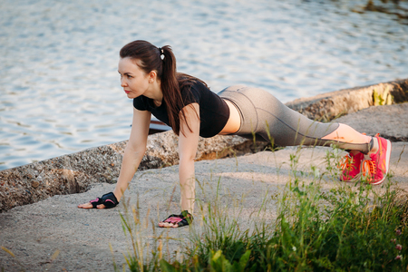 Young Woman Doing Push-Upsin in Park against the lake Stock Photo