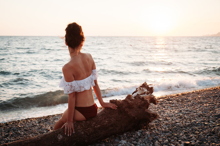 Beautiful young woman sitting on the beach at sunset and meditates Stock fotó