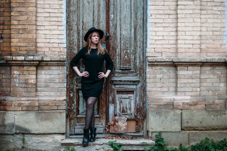 Blonde beautiful girl with long hair, in black dress in hat, stands on the background of vintage antique old wooden door old brick house. For concept design. Banque d'images - 118901175