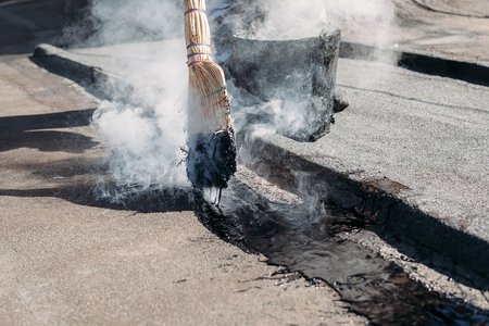 Worker repairs the roof with molten tar from a bucket with a broom. Roof repair tar. Imagens