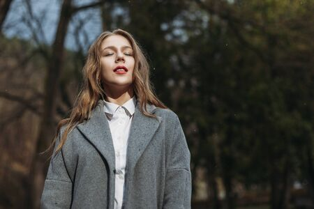 Portrait of a young girl businesswoman in a grey coat posing in Park in autumn Stock Photo