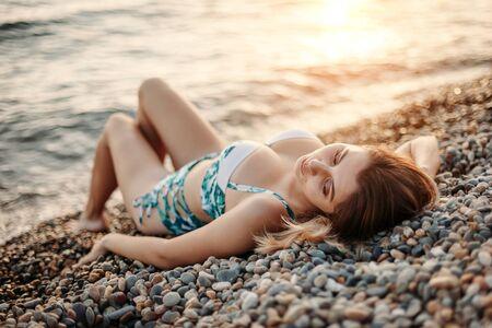 Hermosa chica en traje de baño tomando el sol en el mar Foto de archivo