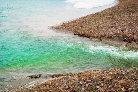 Poisonous, toxic waste flow into the reservoir lake sea ocean. Water pollution. Ecological disaster. Contamination of river plants factory with radioactive waste