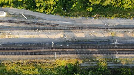 Aerial top down 4k view of the railway along the forest in summer at sunset.