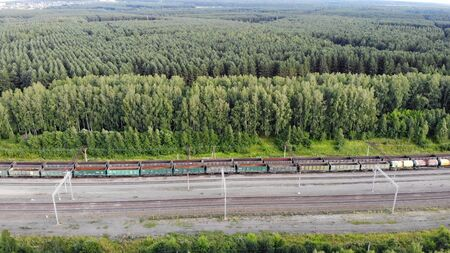 Aerial 4K fly over railway tracks with an empty cargo wagons in summer at sunset.