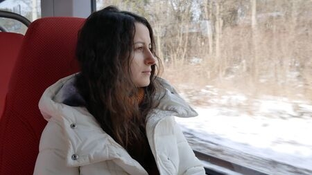 young woman rides sitting in train and looking thoughtfully out the window.