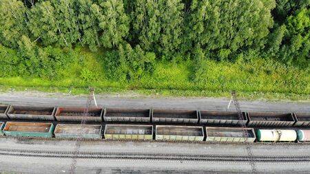 Aerial fly over of railway tracks with an empty cargo wagons in summer at sunset.