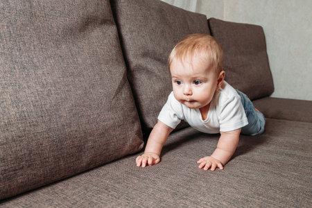 hildhood babyhood and people concept happy smiling little baby boy or girl crawling on sofa
