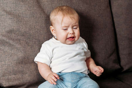 little cute baby boy or girl is capricious and starting crying close up portrait inside