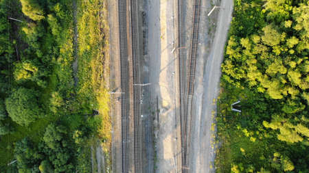 4k Aerial top down view of empty railway along the forest in summer at sunset.