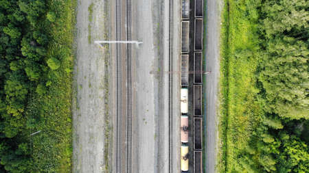 Aerial top down 4k view of railway tracks with an empty cargo wagons in summer.
