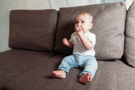 baby sits on couch with a baby's dummy in his mouth