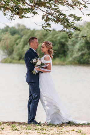 young blonde bride in rustic wedding dress dances with her husband first dance by lake under branches of tree. happy newly married couple.