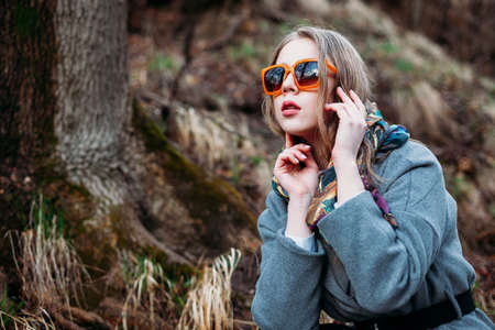 stylish young woman in orange bright glasses posing in a Park in autumn