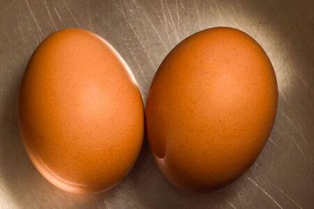 origen animal: dos huevos de color marrón rayado sobre la superficie metálica (colores cálidos)