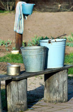 old buckets on wooden bench in garden