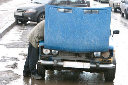 man repairing old car on road