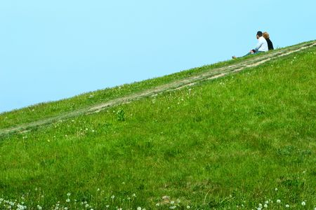 family couple seating on green slope and dreaming something about