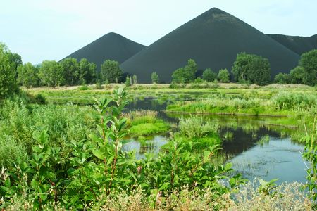 marsh and the black mountains of slags in Kazakhstan, Asia photo