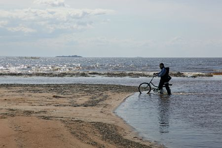 man with bicycle on desert coastline (2) photo