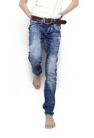 denim jeans: Teenager in blue jeans and a white t-shirt barefoot isolated. With clipping path