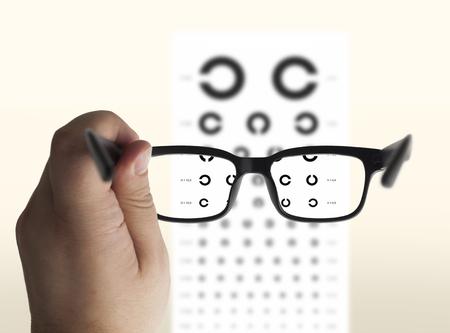 Eyeglasses in hand for eyesight. On the background of a chart test for eyes of Landolt C, isolated Banco de Imagens